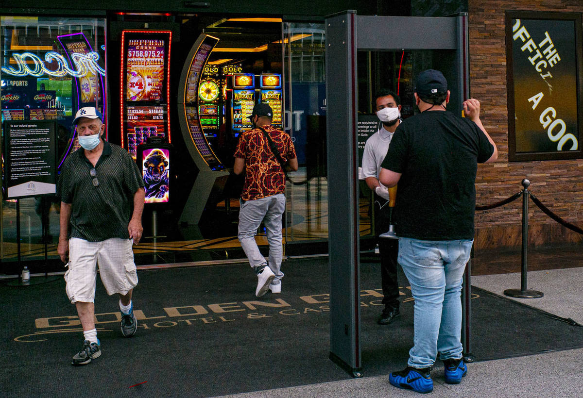 Un hombre se detiene para un chequeo de temperatura en Golden Gate en el centro de Las Vegas el ...