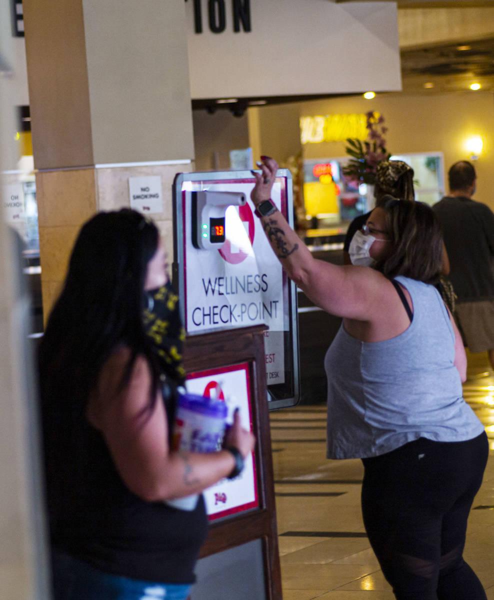 Una mujer sostiene su muñeca para un chequeo de temperatura en Golden Gate en el centro de Las ...