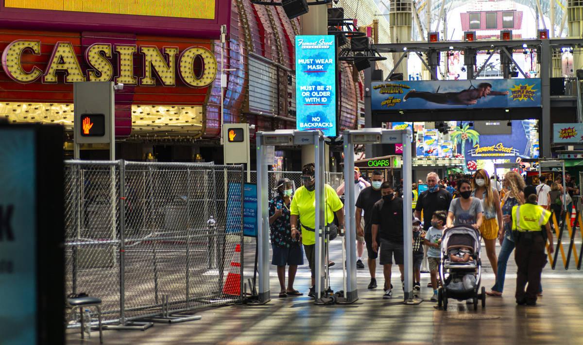 Gente camina a través de los escáneres de temperatura en Fremont Street Experience en el cent ...