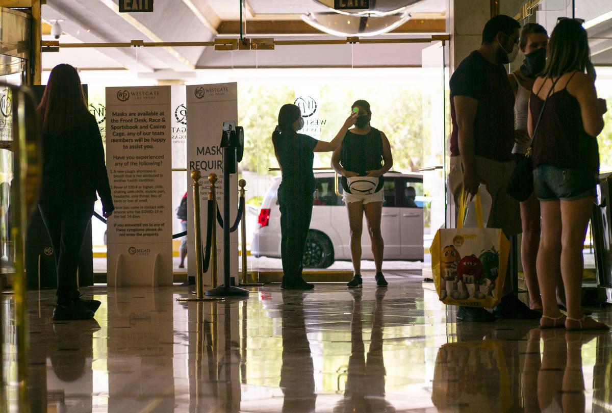 Un hombre se detiene para un chequeo de temperatura en West Gate en el centro de Las Vegas el s ...