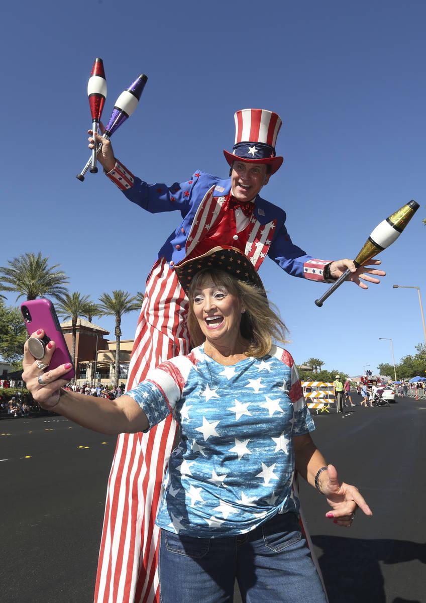 Kathy Koch se toma una foto con un hombre vestido de Tío Sam durante el 25º Desfile Patrióti ...