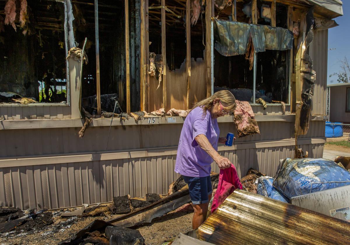 Claudia Arevala clasifica los restos de un incendio en su casa en el Parque de Casas Móviles T ...