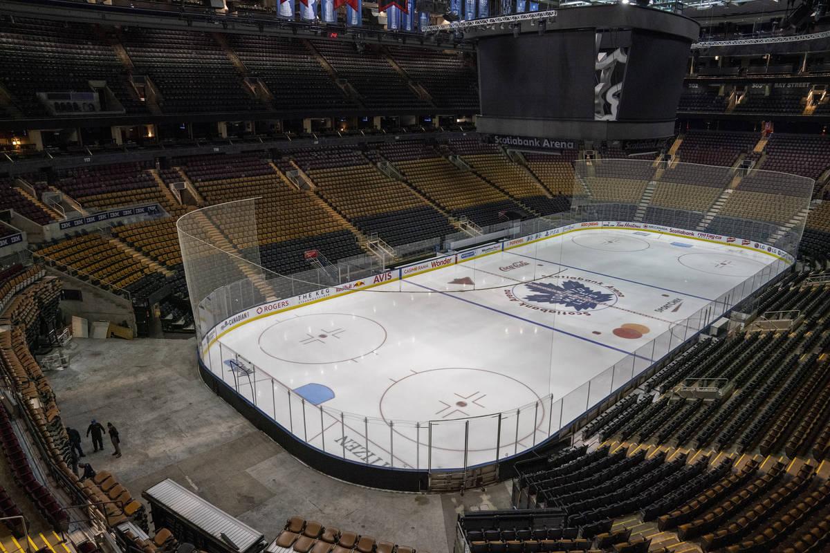 Trabajadores preparan el montaje de la arena para el partido de hockey de la NHL de los Maple L ...