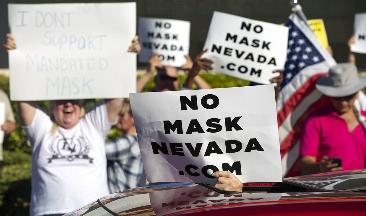 """Un manifestante se acerca a los coches que pasan durante la """"No Mask Protest"""" en la intersecc ..."""
