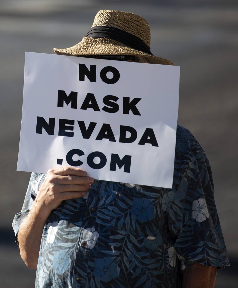 """Un manifestante se cubre la cara con un letrero durante la """"No Mask Protest"""" en la intersecci ..."""