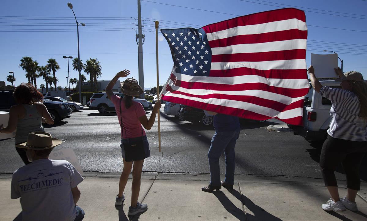 """Faith Muello, segunda a la izquierda, sostiene una bandera estadounidense en la """"No Mask Prot ..."""
