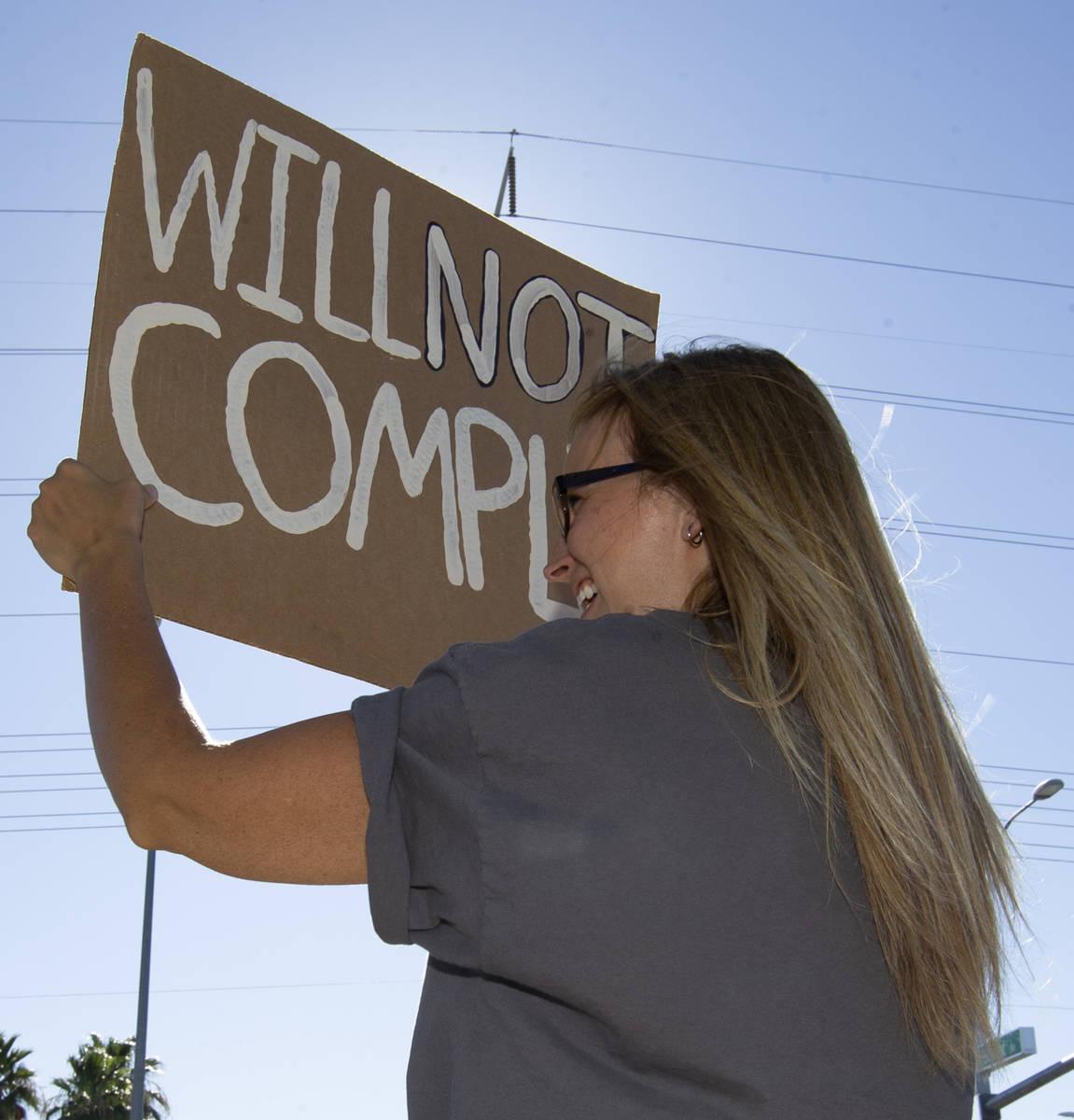 """Anji Gardiner sostiene un cartel que dice """"No Cumpliré"""" durante la """"No Mask Protest"""" en la ..."""