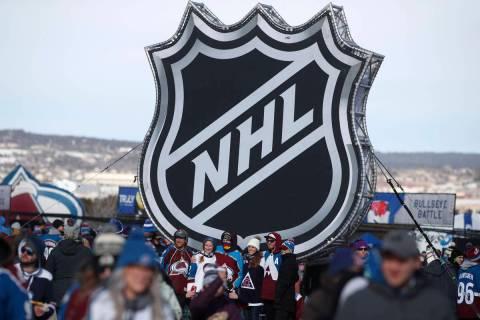 En esta foto del 15 de febrero de 2020, aficionados posan bajo el logo de la liga NHL en una ex ...