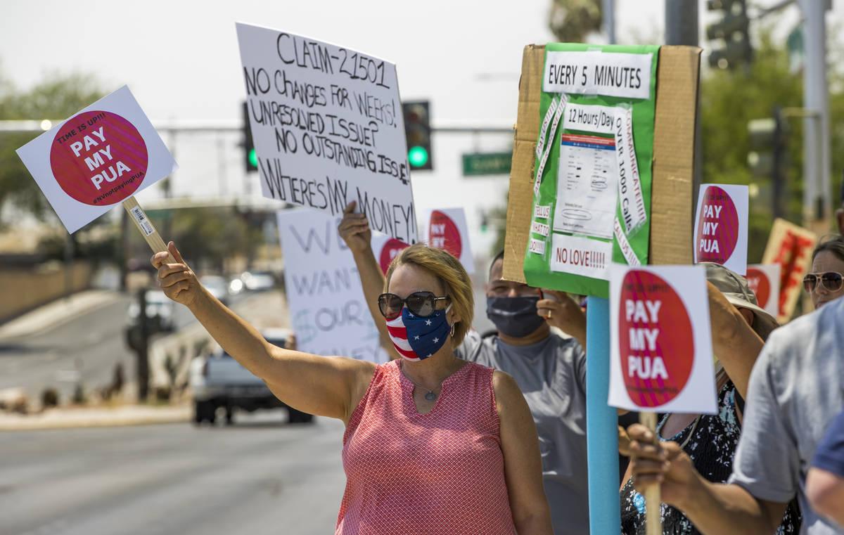 Trabajadores temporales se reúnen con carteles y saludan a los automovilistas que pasan por la ...