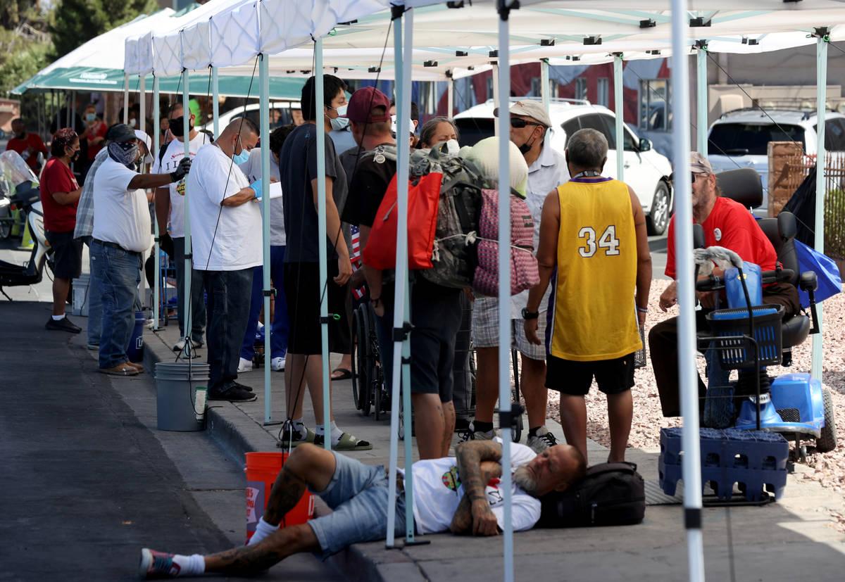 Gente hace fila para una distribución de alimentos en SHARE Village, antes conocido como Veter ...