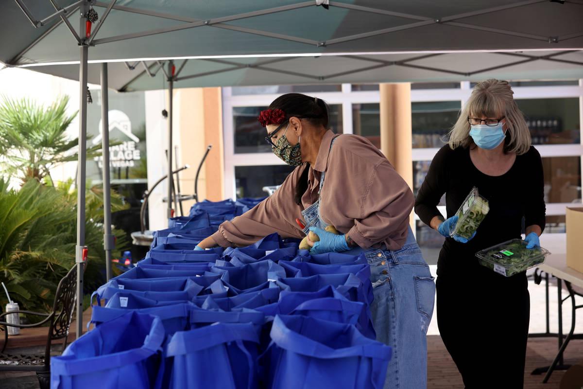 Las voluntarias Carrie Smith, izquierda, y Shannon Oleson preparan bolsas para una distribució ...