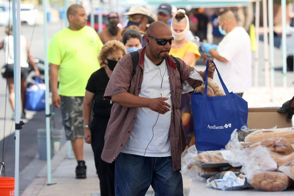 Joaquín Valdez, quien afirma es un desamparado, recoge una bolsa de alimentos en SHARE Village ...