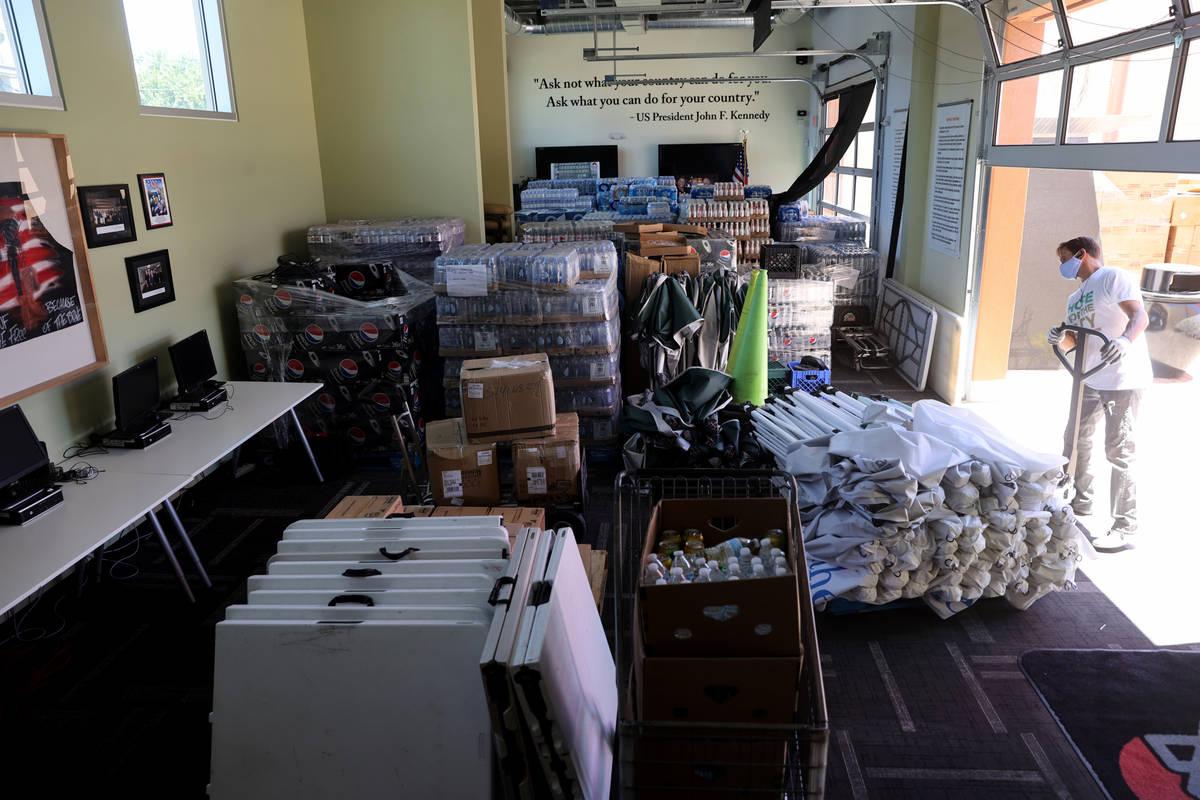 El voluntario Gary Linton carga las estructuras de sombra en el salón multiusos de SHARE Villa ...