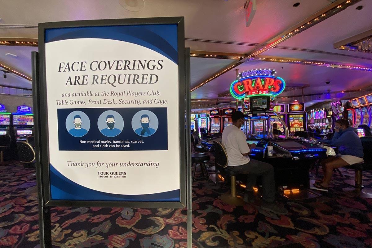 Un letrero notificando a los invitados del requisito de cubrirse su rostro en Four Queens en el ...