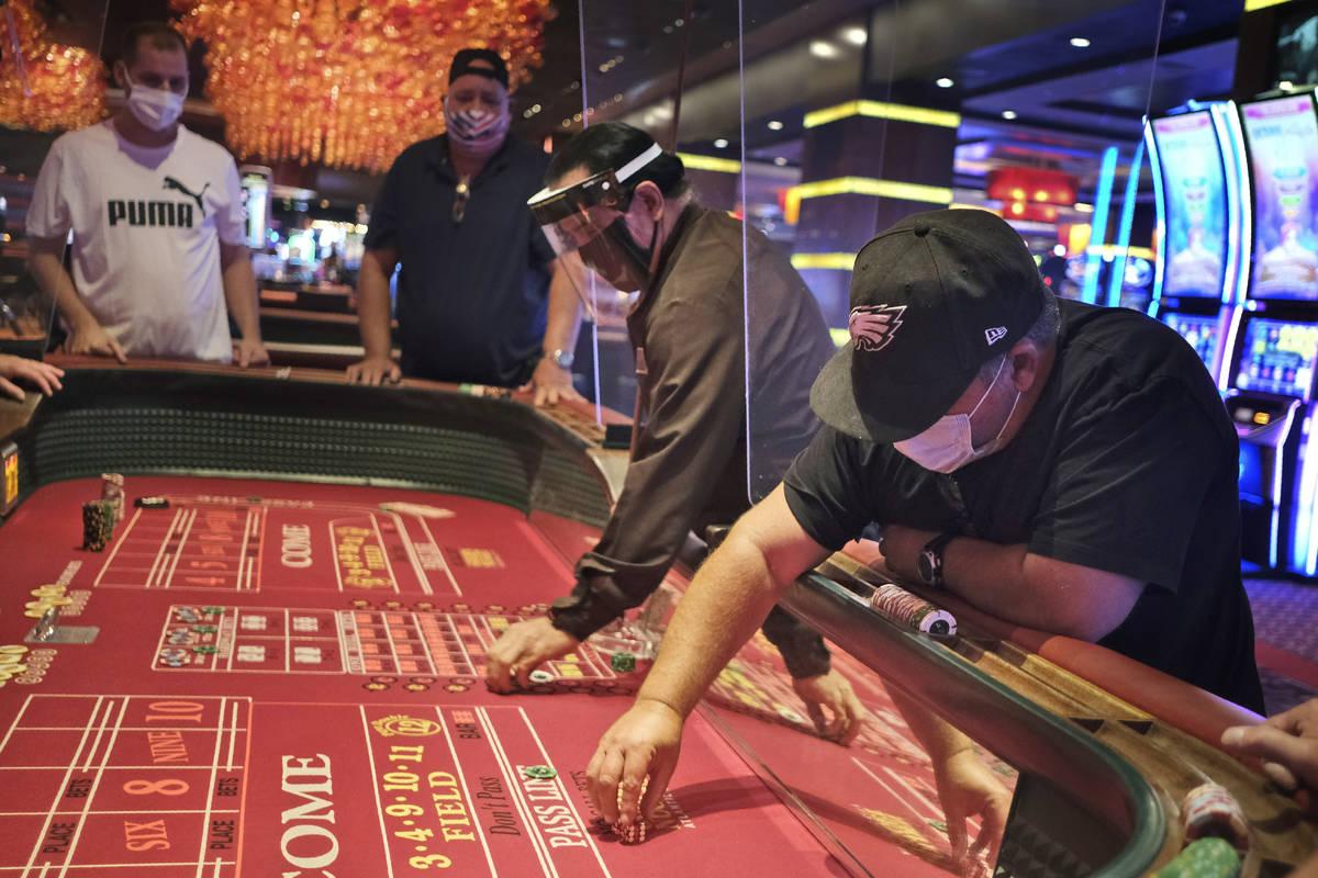 Jugadores y repartidores de dados están separados por tabiques en el Casino Golden Nugget en A ...