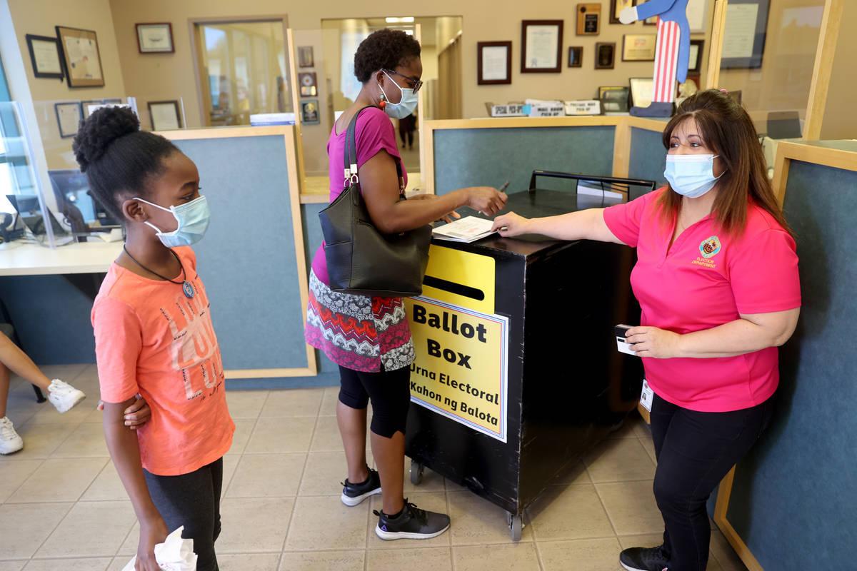 La trabajadora electoral del Condado Clark, Carmen Anaya, a la derecha, ayuda a LaQuetha Lutale ...