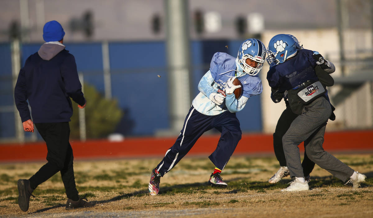 Giovanni Monroe de Centennial corre con el balón durante una práctica de fútbol americano en ...