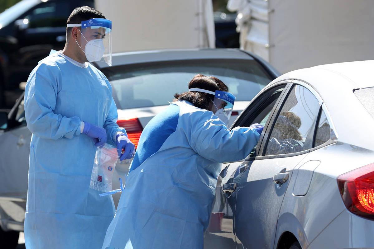 Asistentes médicos certificados por UNLV Medicine hacen una prueba de COVID-19 en la escuela d ...