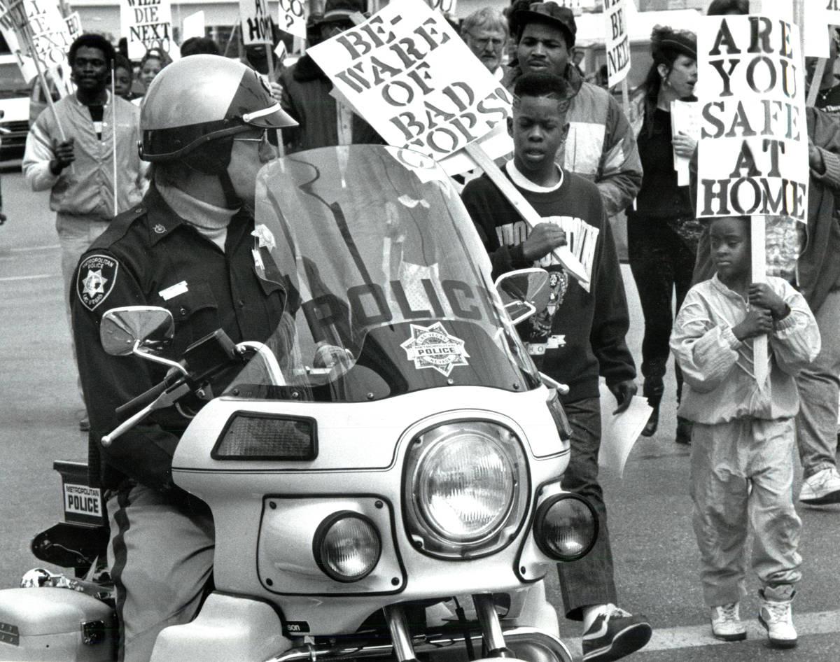 La policía escolta a los manifestantes que protestan por la muerte de Charles Bush durante un ...