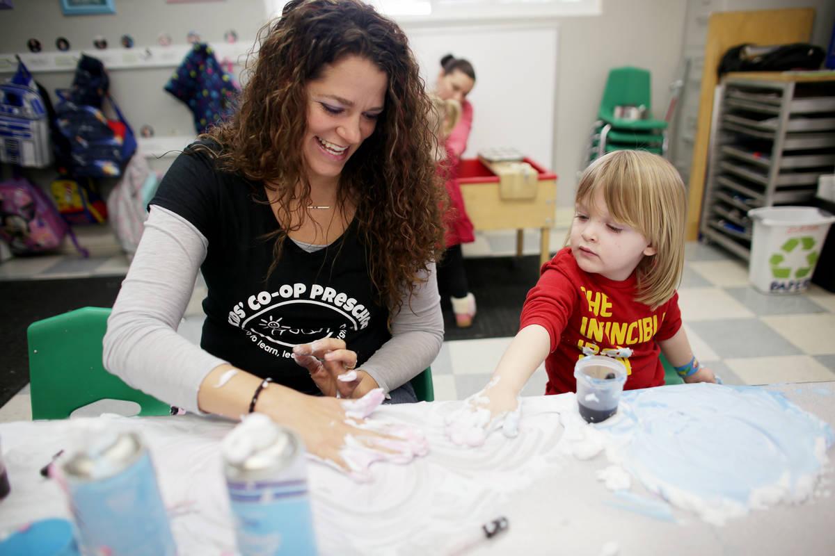 La maestra Bonnie Toth ayuda a Sawyer Karadbil, de tres años, a jugar con crema de afeitar en ...