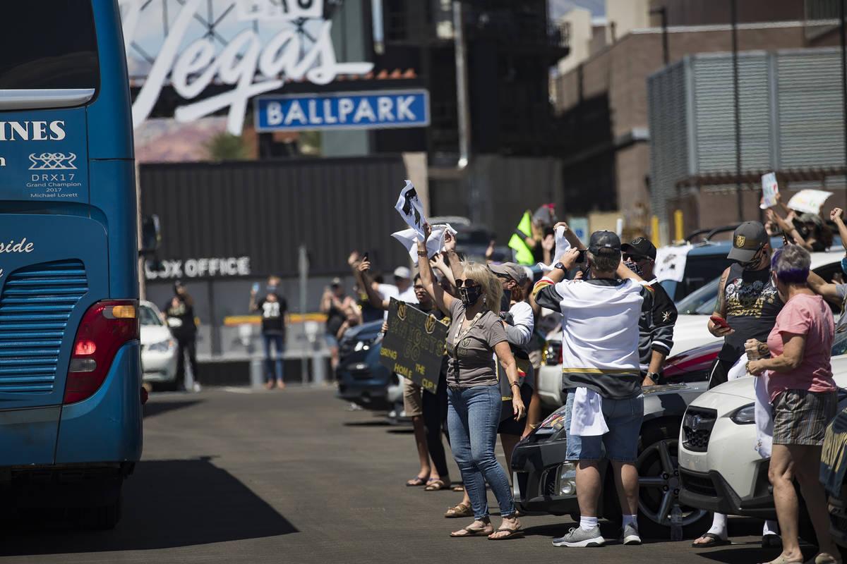 Fans esperan en sus autos para que los Golden Knights pasen en los autobuses dirigiéndose a Ca ...
