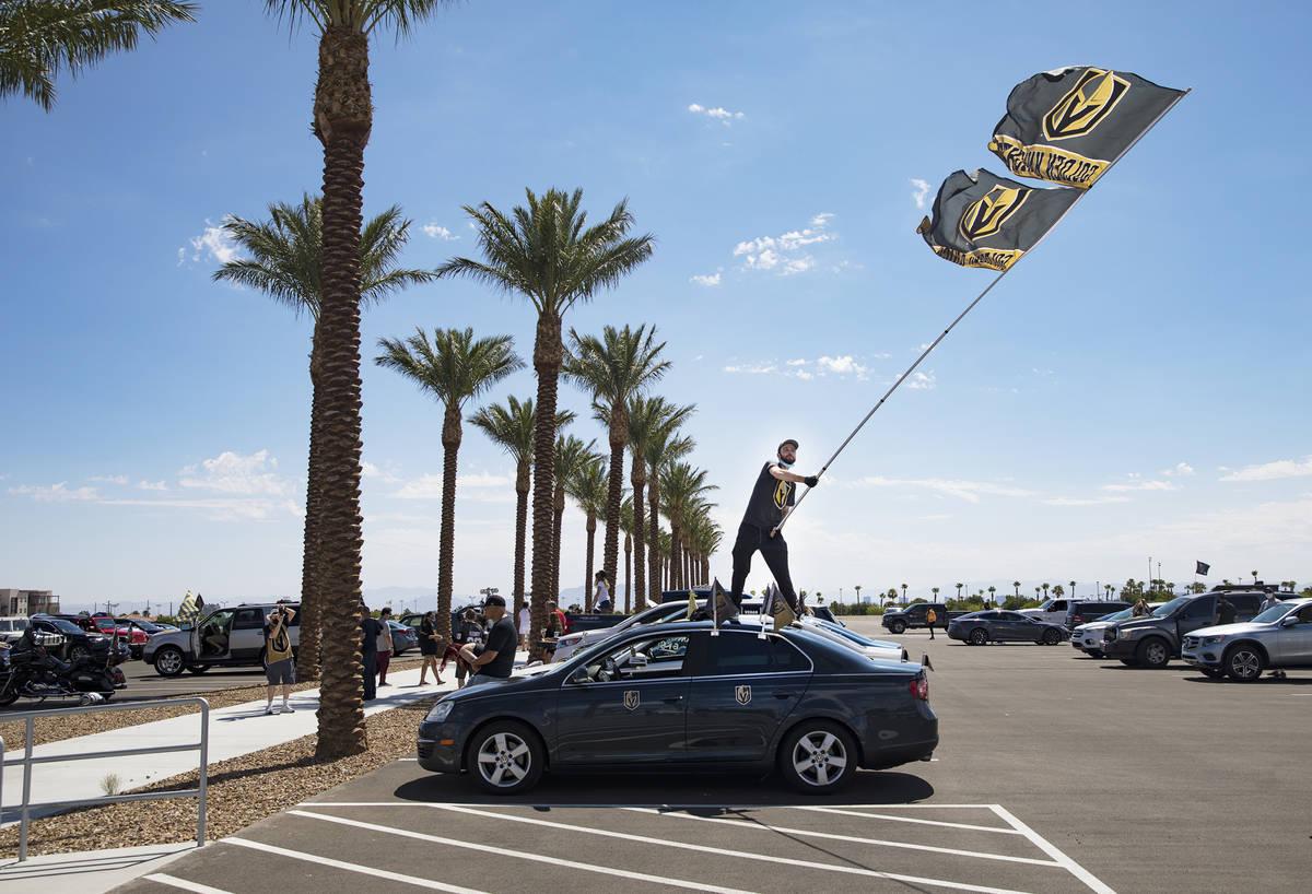 Matt Helfst ondea una bandera mientras espera que los jugadores de los Golden Knights pasen en ...