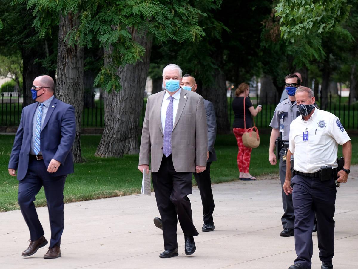 El gobernador Steve Sisolak camina hacia reunión informativa el lunes donde anunció que los b ...