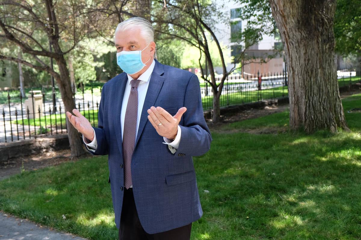 Un enmascaradogGobernador Steve Sisolak habla con los reporteros fuera del Capitolio durante la ...