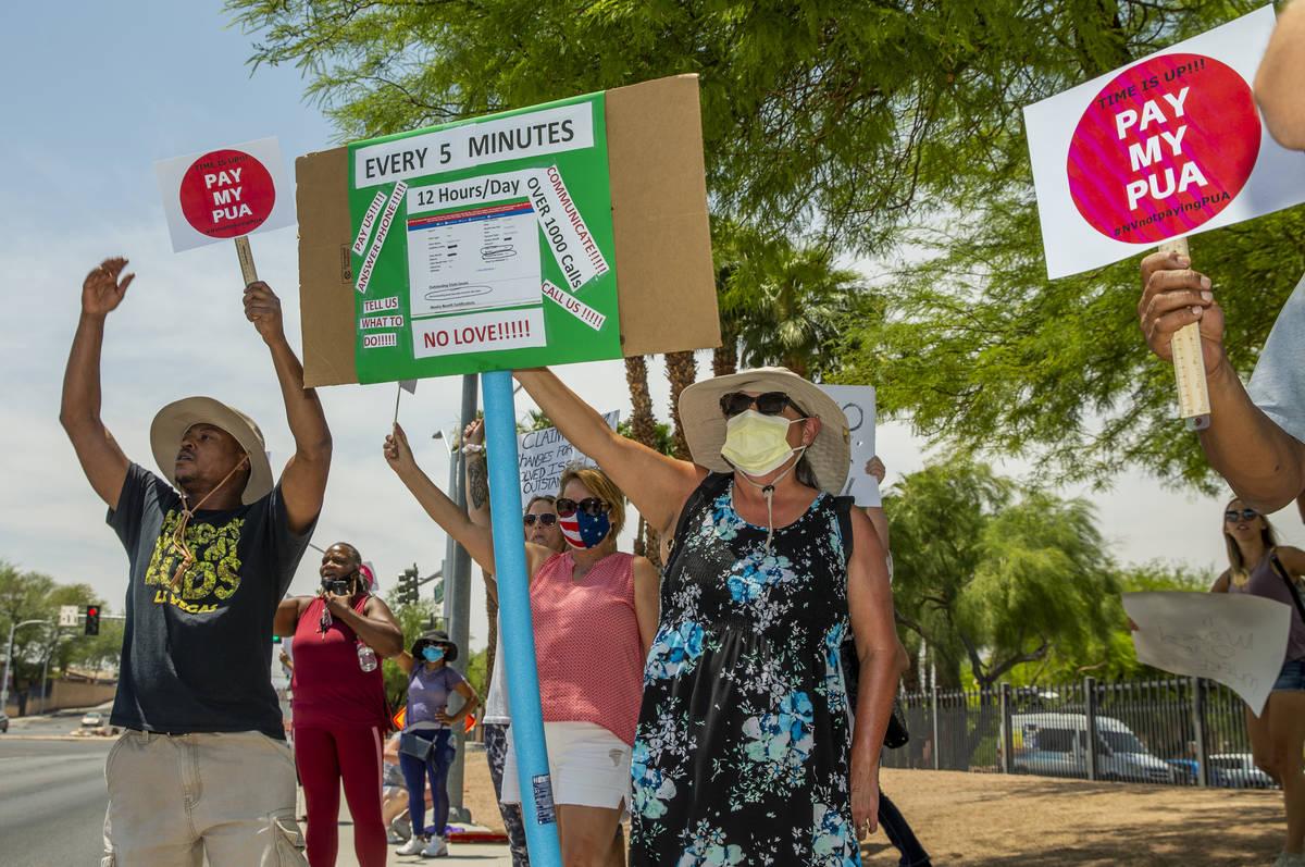 Trabajadores independientes se reúnen con carteles y saludan a los automovilistas que pasan pa ...