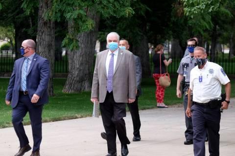 El gobernador Steve Sisolak camina hacia una reunión informativa donde anunció que los bares ...