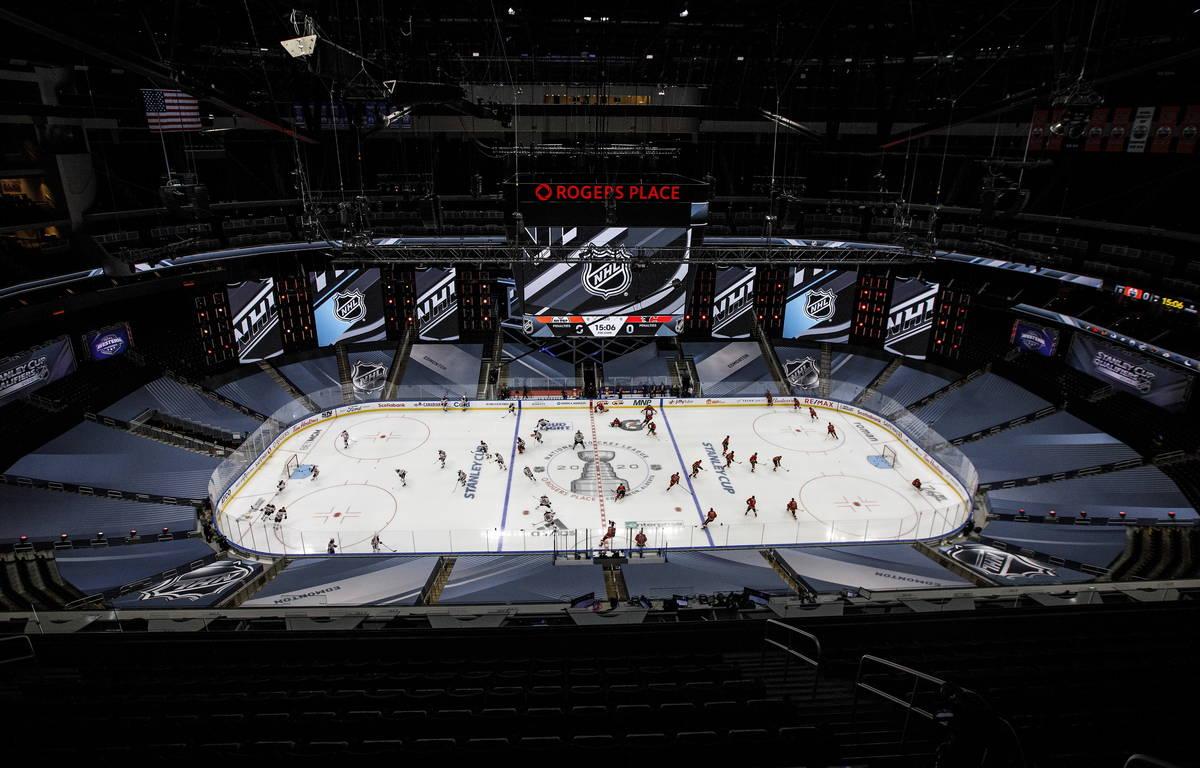 Los jugadores de los Edmonton Oilers y los Calgary Flames calientan antes de un partido de hock ...