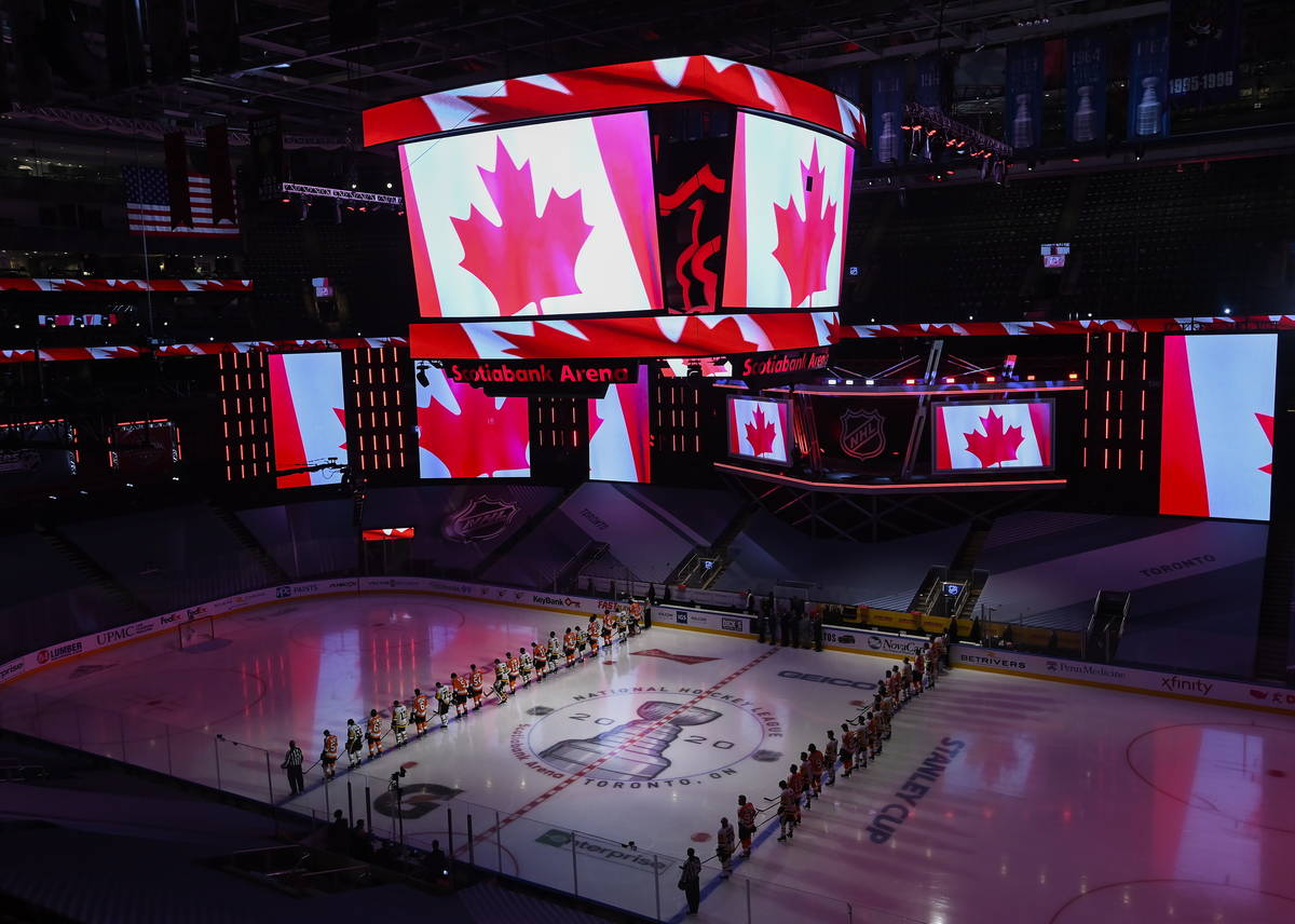 Los Pittsburgh Penguins y los Philadelphia Flyers se alinean para los himnos nacionales antes d ...