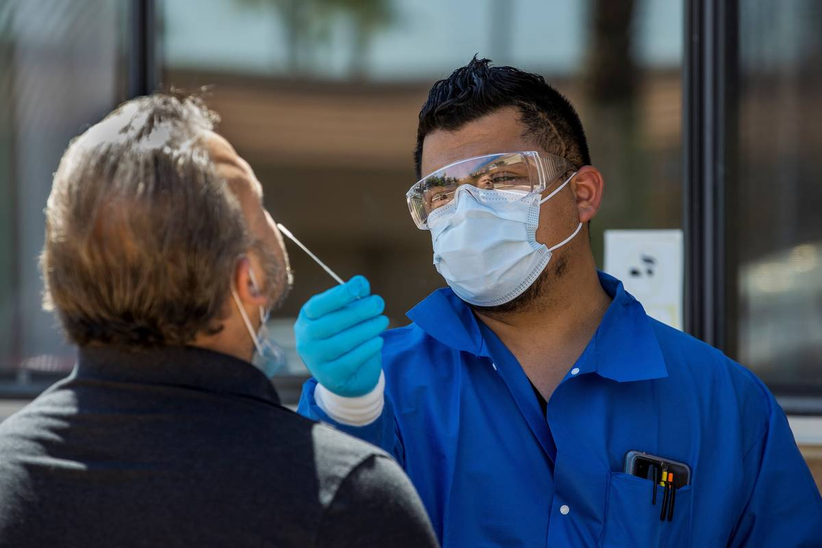 El gerente de practicantes, José Tirana, realiza una prueba de COVID-19 a un paciente en Sahar ...
