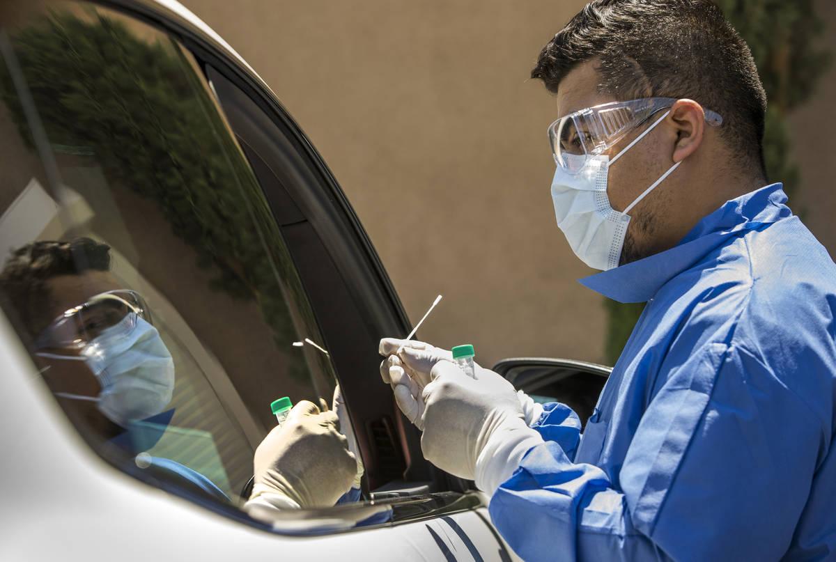 El gerente practicante, José Tirana, le realiza una prueba de COVID-19 a un paciente en el est ...
