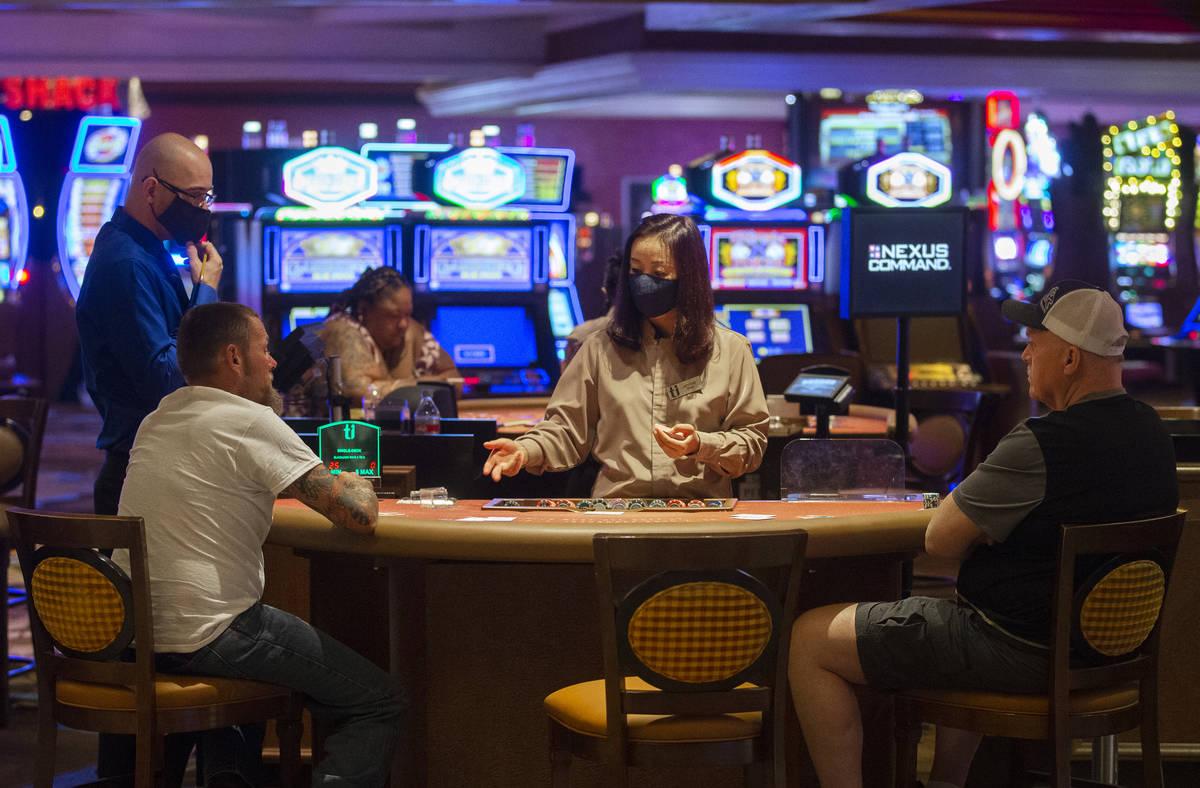 Una dealer con un cubrebocas habla con jugadores de blackjack en Treasure Island el jueves, 4 d ...
