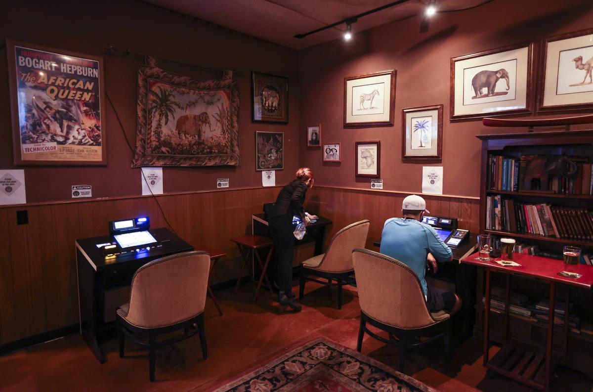 El mesero Silken Widmer desinfecta un dispositivo de juego en un salón de Black Mountain Grill ...