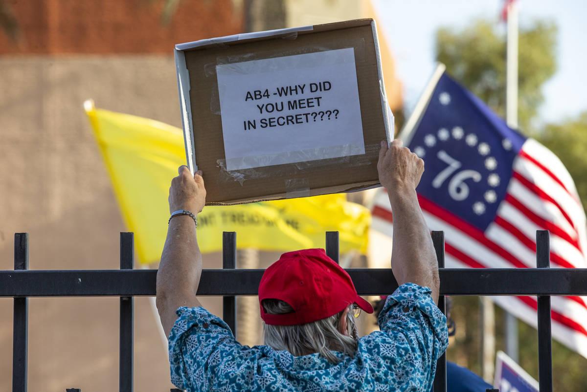 Un manifestante con un letrero frente al edificio Grant Sawyer para expresar su oposición a la ...