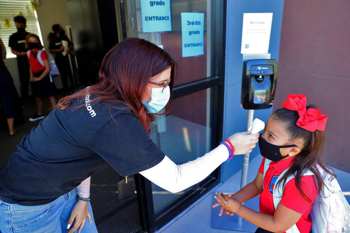 Lianna García se frota las manos con desinfectante mientras le toma la temperatura a Vanessa S ...
