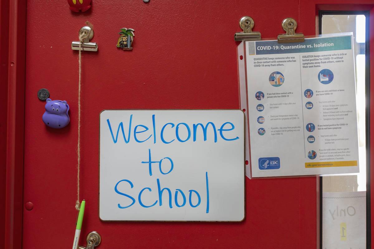 Un letrero da la bienvenida a los estudiantes a la escuela junto a una guía de COVID-19 en la ...