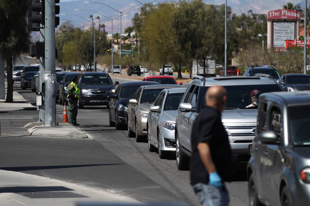 Cientos de personas en sus vehículos esperan recibir comida del Banco de Alimentos Three Squar ...