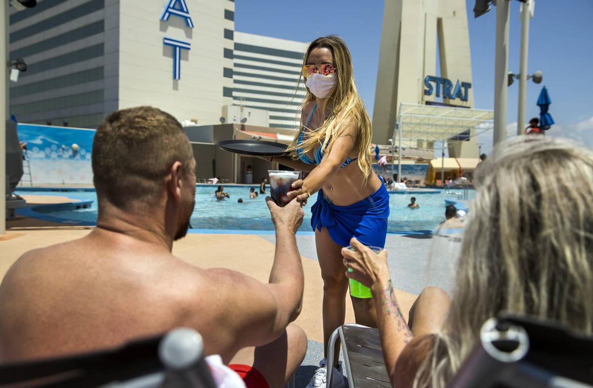 La camarera de cócteles de la piscina, Briana Carroll, en el centro, sirve bebidas a E.J. Morr ...