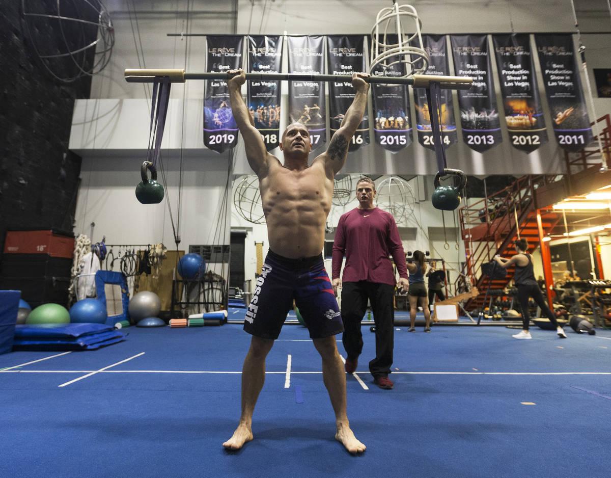 El gimnasta Mirek Niepielski, izquierda, hace sentadillas bajo la supervisión de Steve McCaule ...