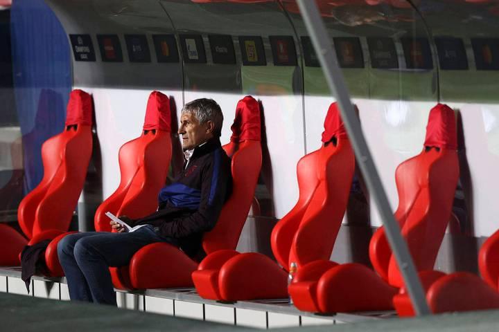 El entrenador en jefe del Barcelona, Quique Setien, se sienta en el banco antes del inicio de l ...