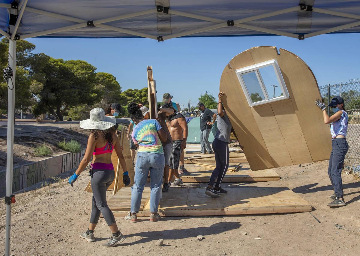 """Miembros de """"Food Not Bombs"""" y del """"Sidewalk Project"""" colocan piezas prefabricadas para constru ..."""