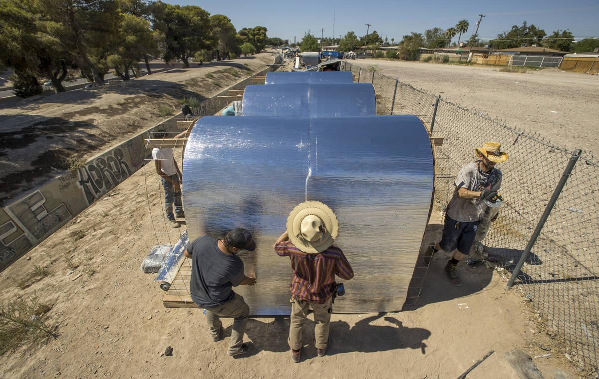 (Desde la izquierda) Tyler Teresi, Nick Cantu y Richard Ward aseguran una capa de aislamiento c ...