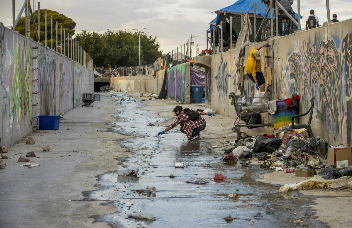 Isabel Coultas, izquierda, y Elijah Mercer recogen basura en un canal de mitigación de agua co ...