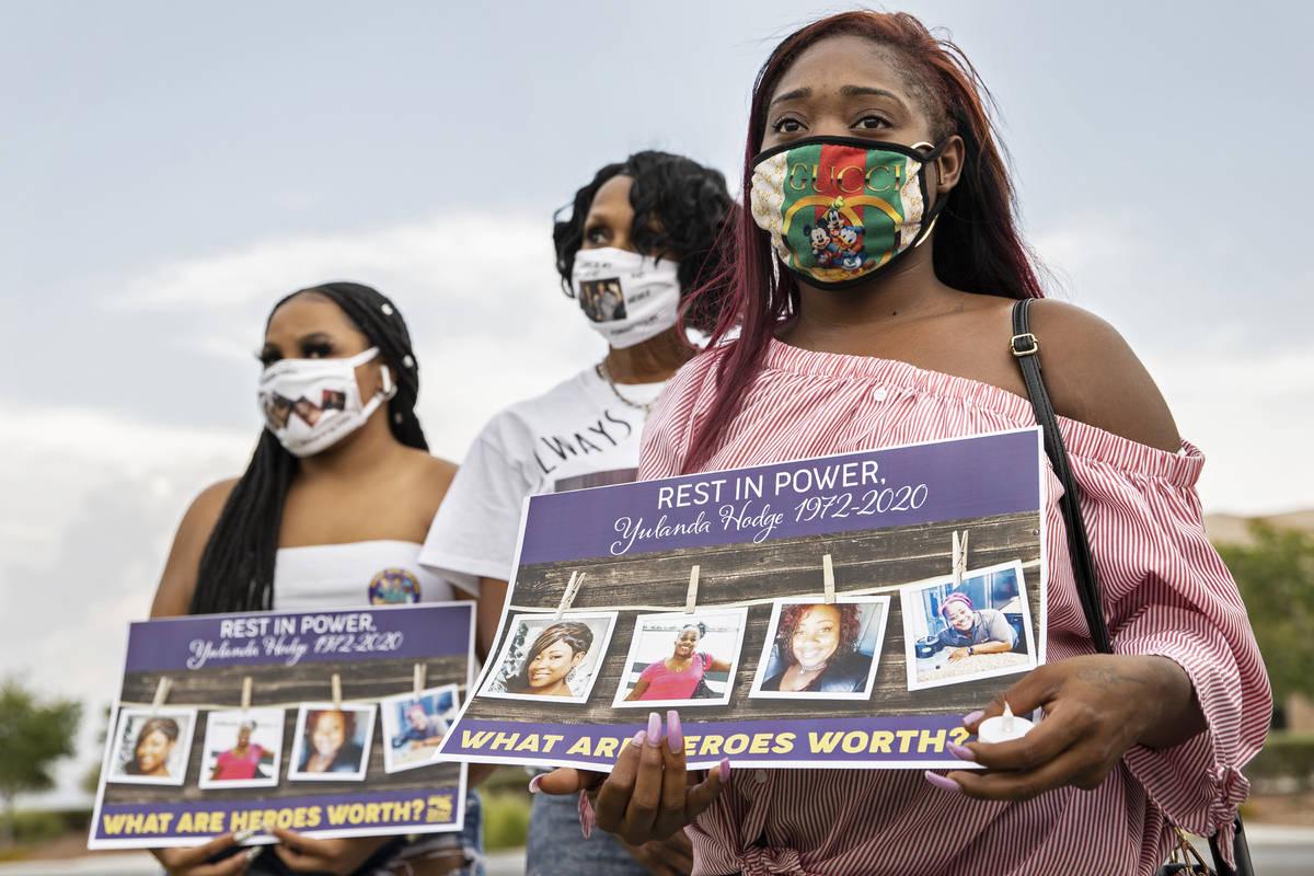 Dejanae Brown, de 23 años, hija de la trabajadora de salud Yulanda Hodge, escucha a un orador ...