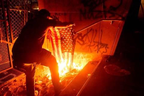 Un manifestante de Black Lives Matter quema una bandera estadounidense frente al Palacio de Jus ...
