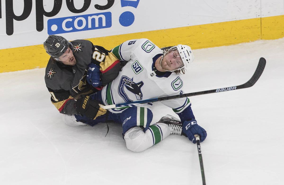 Nick Cousins (21) de los Knights de LV, y Brock Boeser (6) de los Canucks de Vancouver, se enre ...