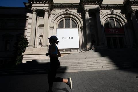 Una mujer pasa junto a una pancarta del artista Yoko Ono en el Museo Metropolitano de Arte, el ...